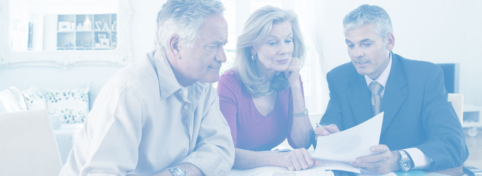 elderly-couple-looking-at-papers-with-advisor